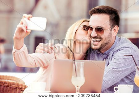Lovely smiling couple taking selfie with smart phone while sitting in cafe.