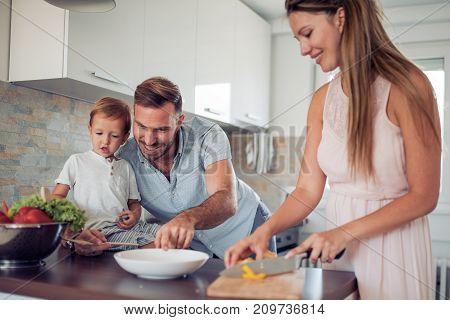 Happy family in the kitchen preparing fresh vegetables.