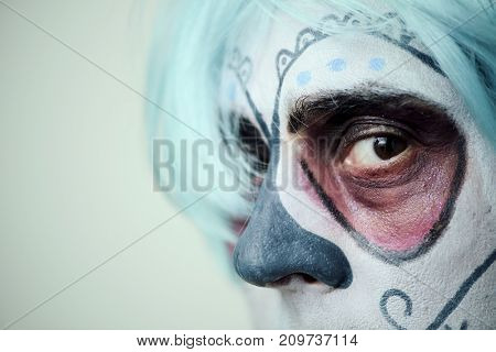 closeup of a person with a mexican calaveras makeup and short blue hair