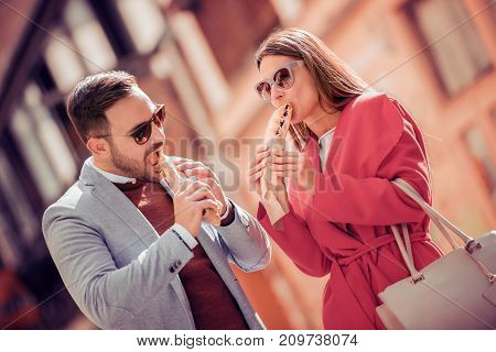 Young couple in love guy and girl sitting and eating sandwich after shopping.