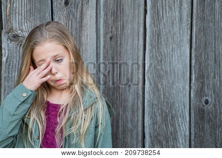 young blond girl rubbing eye with funny facial expression with weathered barn wood background poster