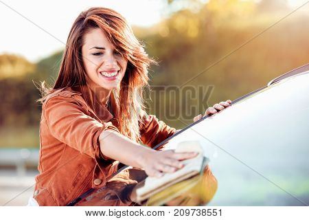Young woman driver dry wiping her car with microfiber cloth after washing it cleaning auto.