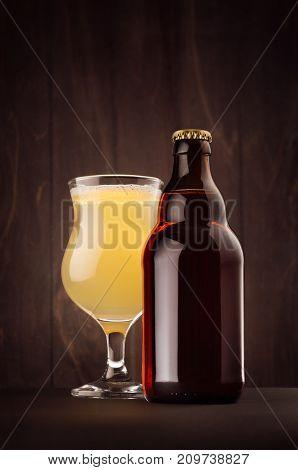 Brown beer bottle belgian steinie and glass tulip with muddy weizen on dark wood board vertical mock up. Template for advertising design branding identity.