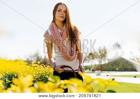 a young lovely red-haired girl is walking with her dog in the park, around a lot of greenery and sun