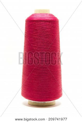 Red spool or reel of thread for sewing on white background using for fabric textile industry and sewing productionclose up shot.