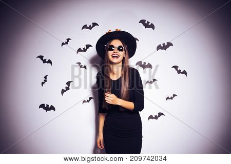 young sexy gothic woman in the image of a witch in halloween, in a big black hat, adorned with yellow leaves, wearing sunglasses, laughing