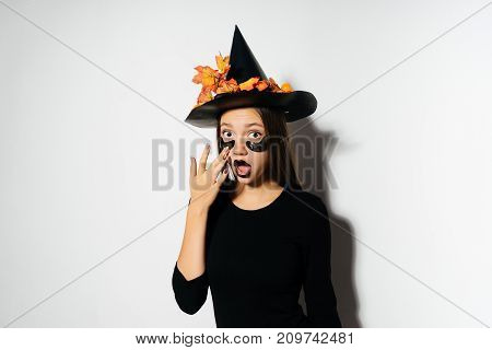 A young sexy gothic woman in the shape of a witch in halloween, in a big black hat, adorned with yellow leaves, looks surprised