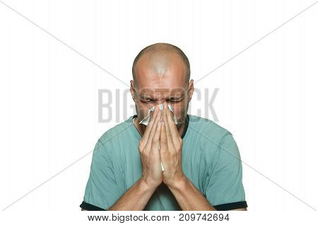 Young bald man sick from common cold flu blowing his nose with paper tissue isolated on white background