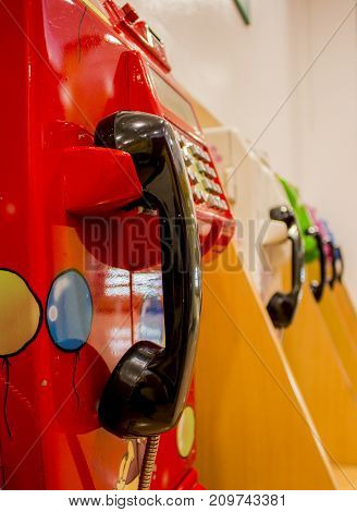 Close up of black ear phone and red payphone (public telephone).