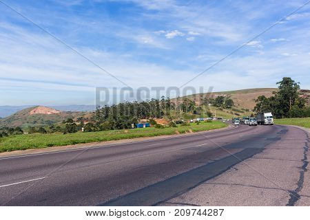 Trucks and vehicles on steep road highway hill climb in countryside landscape.