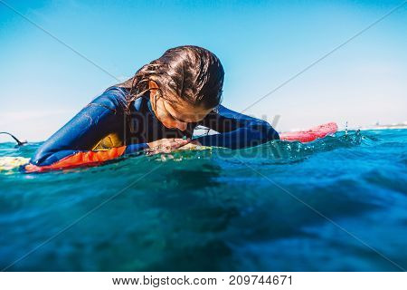 Surf girl in wet suit relax on surfboard. Woman with surfboard in ocean during surfing.
