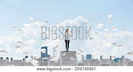 Woman in casual clothing standing among flying paper planes with speaker in hand and with skyscape on background. Mixed media.