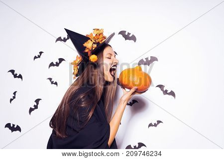 a young sexy gothic woman in the form of a witch in halloween, in a big black hat, adorned with yellow leaves, holds a pumpkin and screams at her