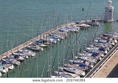 VENICE ITALY - SEPTEMBER 21 2017: Yacht harbor and lighthouse off the coast San Giorgio island. It is small island of the Venetian Lagoon opposite St. Mark's Square