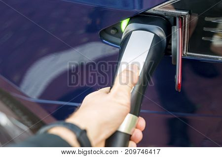 Man's Hand Holding Modern Electric Car Charger Outlet.
