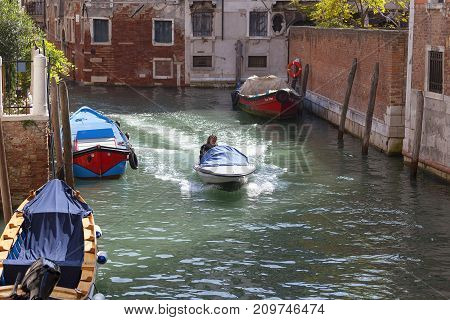 VENICE ITALY-SEPTEMBER 22 2017: Motorboat flowing through a side narrow canal. Motorboats are one of the ways of transportation in Venice mostly used as a taxi