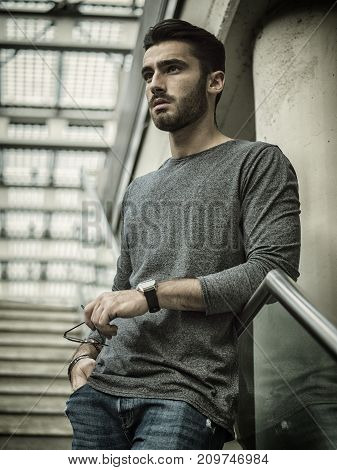 Handsome young man walking on stairway looking away