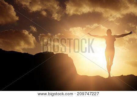 Happy sportswoman is raising arms  against cloudy sky landscape