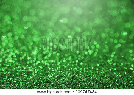 Green bright abstract bokeh background. Sparkle texture for birthday card or christmas new year Saint Patrick's Day party and other holidays invitation backdrop.