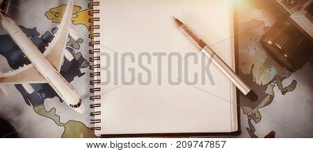 Overhead view of diary with toy airplane and coffee cup on map