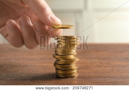 Woman stacking coins on wooden table, closeup