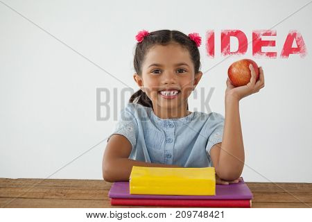 Digital composite image of pink idea text against schoolgirl holding a red apple against white background