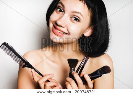 smiling girl with black short hair chooses which brush to make the make-up, isolated