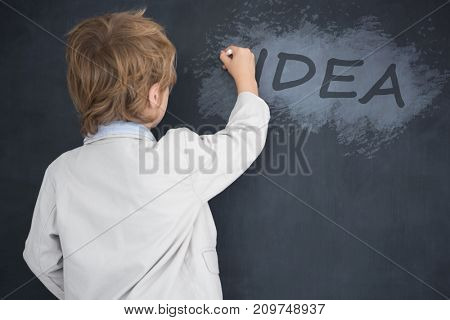 Cute pupil writing on board against digital composite image of idea text on black spray paint