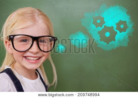 Cute pupil smiling against digital composite image of gears on blue spray paint