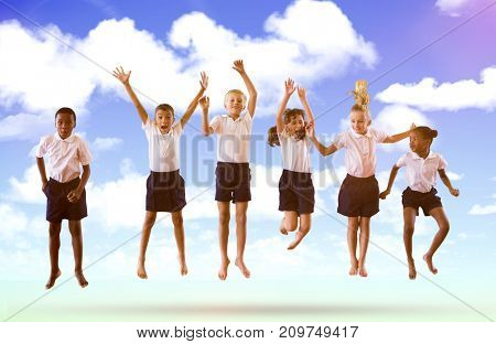 Full length of students in school uniforms jumping against blue sky