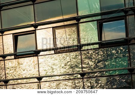 Reflection of sea with sun glares seen in the glass facade of railway station in Adler Russia