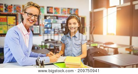 Portrait of teacher with student writing on book against interior of empty classroom