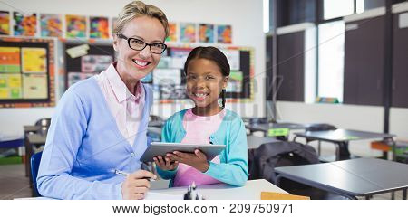 Portrait of student with teacher holding digital tablet against interior of empty classroom