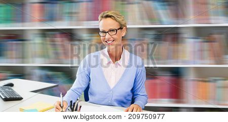 Portrait of teacher writing on book against shelf of books