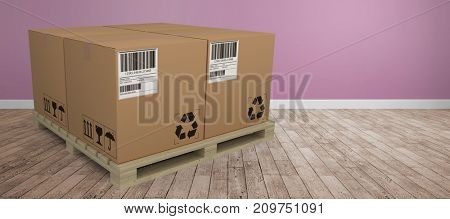 Cardboard boxes arranged on wooden pallet against room with wooden floor