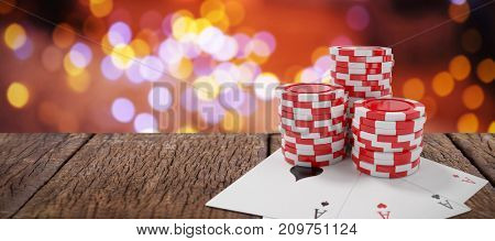 Red casino tokens with playing cards against composite image of table