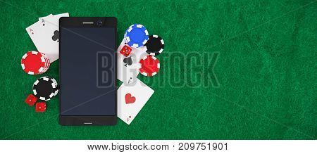 Mobile phone with playing cards and stack of casino tokens against green painted paper