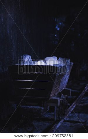 Salt old wooden mine cart on rails full of crystal chunk cubes dark mysterious photography resembling a dwarf magical hideout