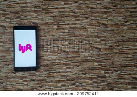 Los Angeles, USA, october 19, 2017: Lyft logo on smartphone screen on stone facing background