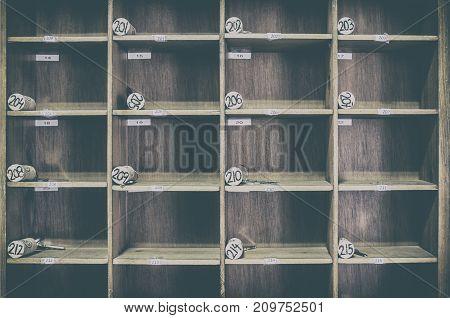 Vintage rural hotel front desk key rack with numbered corks. Focus on the top row of keys. Rural tourism concept