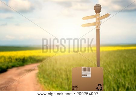 Cardboard box with road sign against scenic view of empty path passing through fields