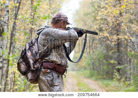 hunter in camouflage taking aim from a shotgun in the wildfowl