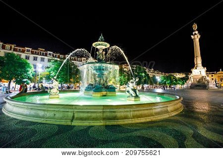 Lisbon downtown, Baixa District. Urban scene by night. Spectacular baroque fountain and statue of Dom Pedro IV in Praca Dom Pedro IV or Rossio Square in Lisbon, Portugal, Europe.