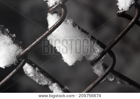 snow on the fence. close-up . In the park in nature