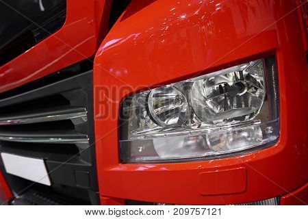 MOSCOW, SEP, 5, 2017: Close up view on red truck MAN front light and radiator grille hood. Truck light. Car light lamp. Aggressive car design. Truck cabin close up