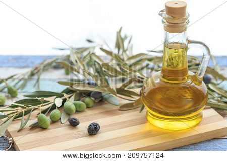 Olive oil in glass with olives and olive branches on cutting board