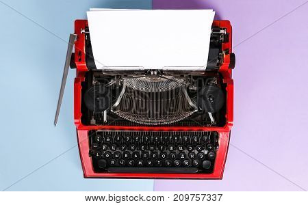 Vintage red typewriter over a pastel background. Red typewriter. The writer's tool