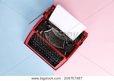 Photo vintage red typewriter over a pastel background. Red typewriter. The writer's tool