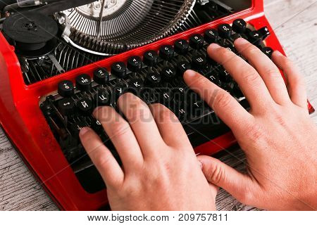 New photo of vintage red typewriter maschine on the table and author hands on. Closeup horizontal photo