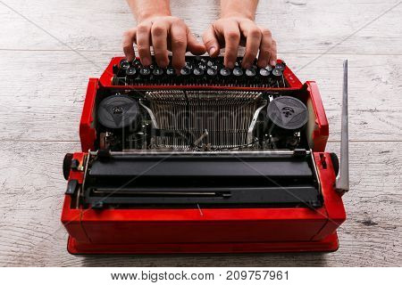 Vintage red typewriter with hands on the table. Close up horizontal image